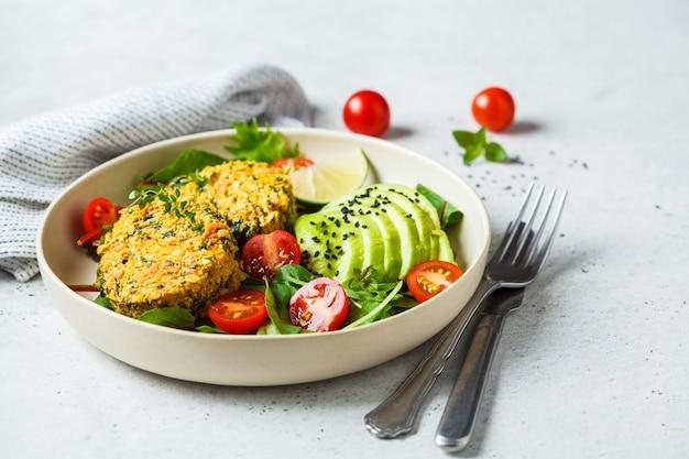 Kürbis- und quinoakoteletts des strengen vegetariers mit salat in einer weißen platte. Premium Fotos