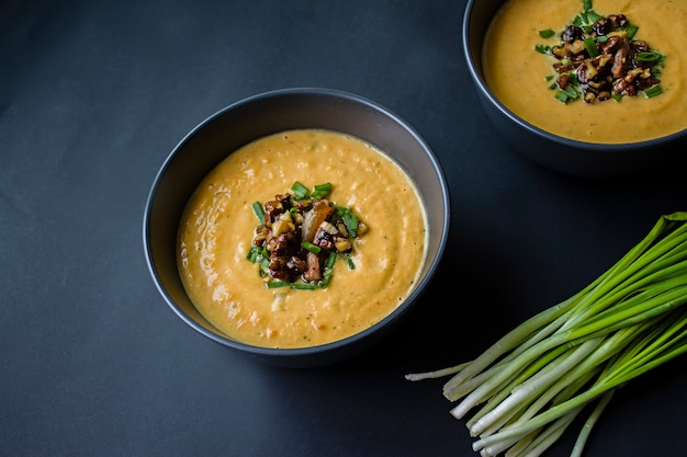 Kürbiscremesuppe mit kräutern und nüssen, serviert in einer dunklen schüssel. richtiges und gesundes essen. vegetarisches gericht. Premium Fotos