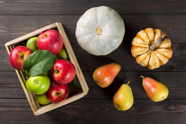Kürbise mit reifen äpfeln in einem kasten und birnen auf dunklem hölzernem. Premium Fotos