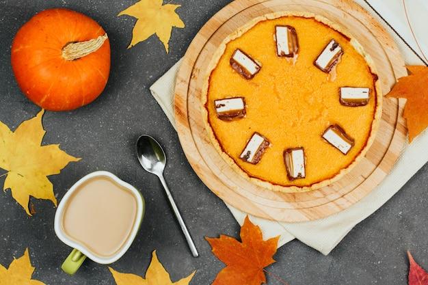 Kürbiskuchen auf einem hölzernen brett, kleinen orange kürbisen, herbstahornblättern und einem tasse kaffee Premium Fotos