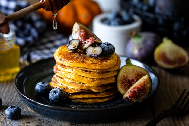 Kürbispfannkuchen mit sirup oder honig, leinsamen, feigen, blaubeeren in einem dunklen teller auf dem tisch Premium Fotos
