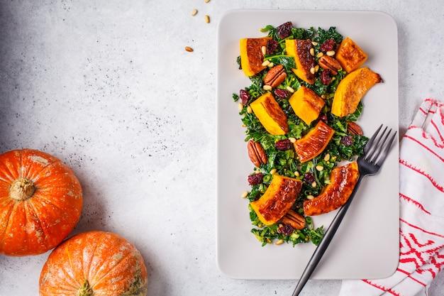 Kürbissalat mit nüssen, moosbeeren und kohl in einer rechteckigen platte, draufsicht. Premium Fotos
