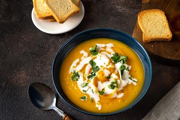 Kürbissuppe mit sahne und petersilie auf dunkler rustikaler tabelle Premium Fotos