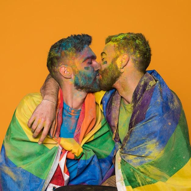 Küssende paare von gemalten homosexuellen männern, die in lgbt-flaggen eingewickelt werden Kostenlose Fotos