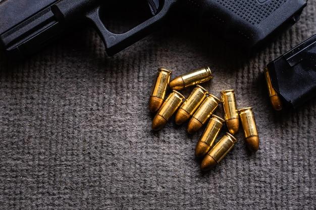 Kugeln und pistole auf schwarzem samtschreibtisch Premium Fotos
