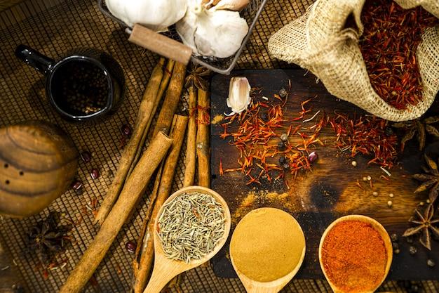Kulinarische gewürze mit kräutern und gewürzen auf rustikalen hintergrund Premium Fotos