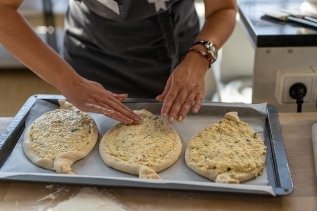 Kulinarische meisterklasse. nahaufnahme von den leutehänden, die khachapuri zubereiten. traditionelles georgisches käsebrot. georgisches essen. große unerkennbare familie, die nah hände oben kocht Premium Fotos