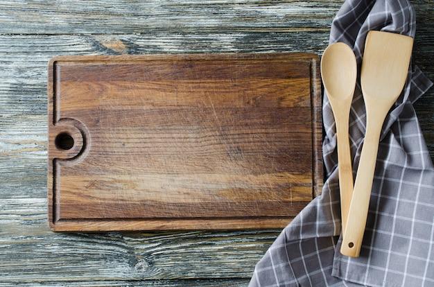Kulinarischer hintergrund mit rustikalem küchengeschirr auf weinleseholztisch. Premium Fotos