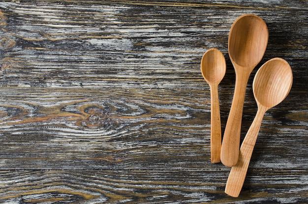 Kulinarischer hintergrund mit rustikalen löffeln auf weinleseholztisch. Premium Fotos