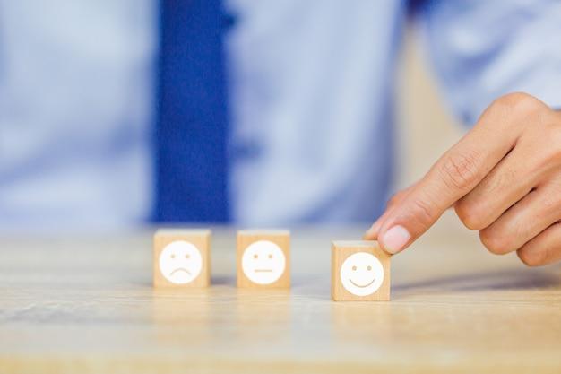 Kunde, der smileygesicht emoticon auf hölzernem würfel drückt Premium Fotos