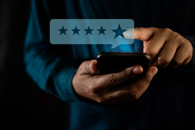 Kundenerlebnis-konzept. ein moderner mann, der über ein smartphone eine sternebewertung für eine positive bewertung erhält Premium Fotos