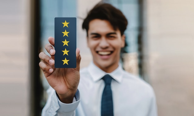 Kundenerlebnis-konzept. glücklicher junger geschäftsmann, der fünf-sterne-bewertung und positive bewertung auf karte gibt. umfragen zur kundenzufriedenheit. vorderansicht Premium Fotos