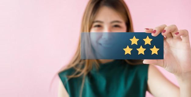 Kundenerlebniskonzept. glückliche lächelnde frau und show-ausgezeichnete bewertung mit fünf stern Premium Fotos