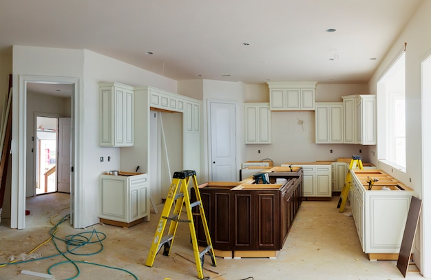 Kundenspezifische küchenschränke in verschiedenen stadien der installationsunterseite für insel in der mitte Premium Fotos