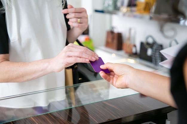 Kundin, die für kauf durch kreditkarte im bekleidungsgeschäft zahlt und der kassiererin über dem schreibtisch eine leere karte gibt. kurzer schuss, nahaufnahme der hände. einkaufs- oder kaufkonzept Kostenlose Fotos