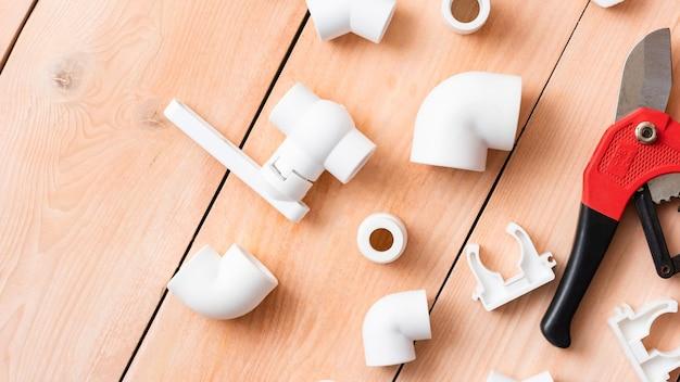 Kunststoffteile auf einem holztisch für das wasserversorgungssystem. draufsicht Premium Fotos