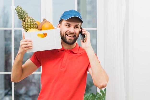 Kurier mit den früchten, die am telefon sprechen Kostenlose Fotos