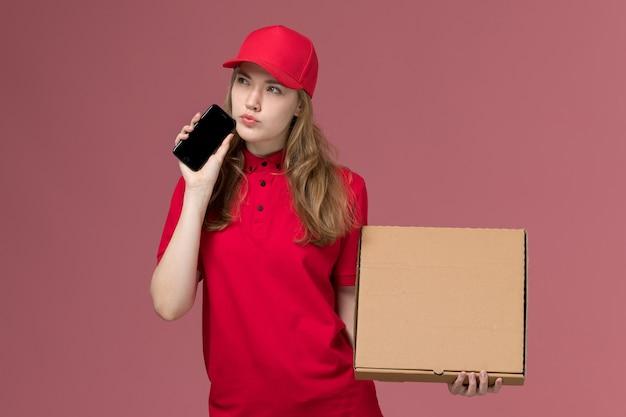Kurierin in roter uniform, die telefon-nahrungsmittelbox auf hellrosa, dienstuniform-dienstarbeiterzustellung hält Kostenlose Fotos