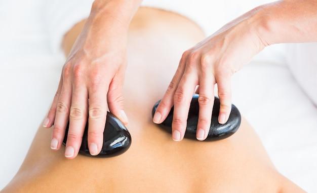 Kurzer masseur, der hot stone massage auf frau zurück gibt Premium Fotos