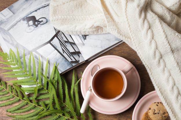 Kuscheliger pullover; buch; teetasse und kekse mit blättern auf dem tisch Kostenlose Fotos