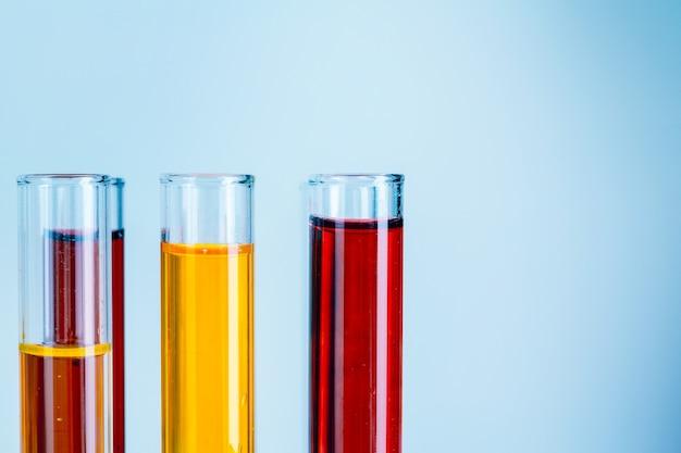 Laborversuchrohre mit den roten und gelben flüssigkeiten auf hellblauem hintergrund Premium Fotos