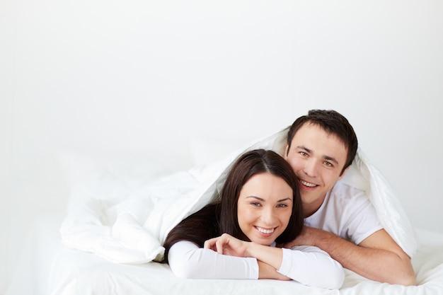 l chelnd paar im bett liegend download der kostenlosen fotos. Black Bedroom Furniture Sets. Home Design Ideas