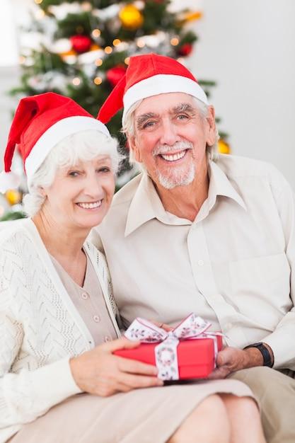 Lächelnde alte Paare, die Weihnachtsgeschenke tauschen | Download ...