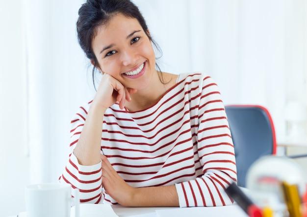 Lächelnde Frau, die am Schreibtisch sitzt Kostenlose Fotos
