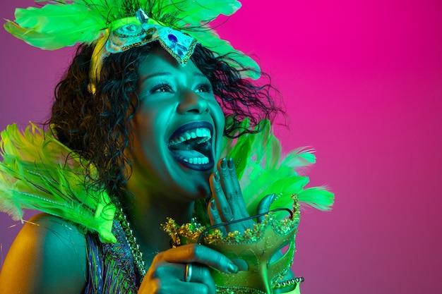 Lachen. schöne junge frau im karneval, stilvolles maskeradenkostüm mit federn, die auf gradientenwand in neon tanzen. konzept der feiertagsfeier, der festlichen zeit, des tanzes, der party, des spaßes. Kostenlose Fotos