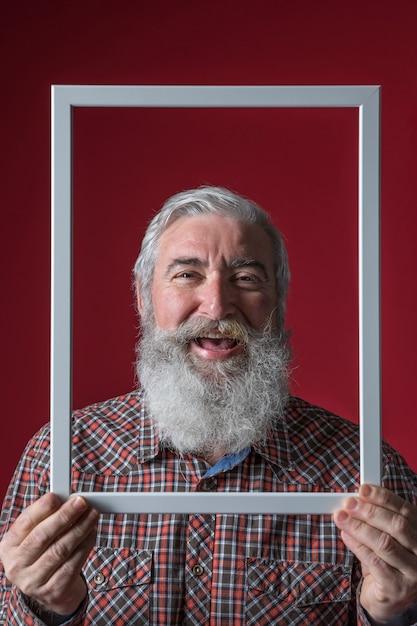 Lachende ältere frau, die weiße rahmengrenze vor seinem gesicht gegen roten hintergrund hält Kostenlose Fotos