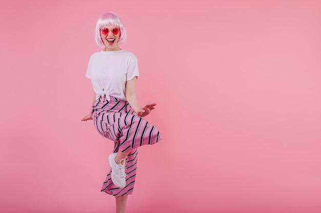Lachende atemberaubende frau in der sonnenbrille, die auf rosa wand tanzt. fröhliches europäisches weibliches modell in glamouröser perücke, die spaß hat Kostenlose Fotos