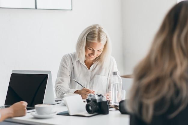 Lachende blonde frau im weißen hemd, das unten schaut, während sie etwas schreibt. innenporträt des beschäftigten freiberuflichen weiblichen spezialisten, der am arbeitsplatz mit laptop und kamera aufwirft. Kostenlose Fotos