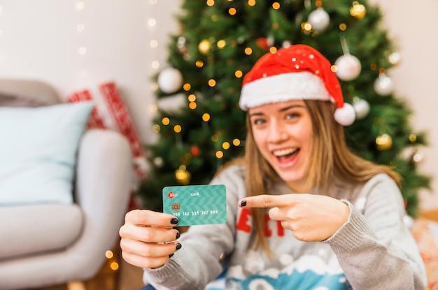 Lachende festliche frau, die auf kreditkarte zeigt Kostenlose Fotos
