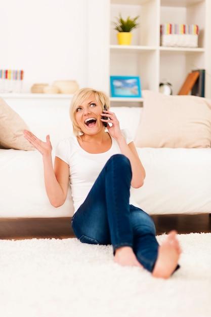 Lachende frau am telefon im wohnzimmer Kostenlose Fotos