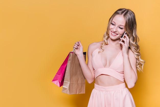 Lachende Frau, die am Telefon beim Einkauf spricht Kostenlose Fotos