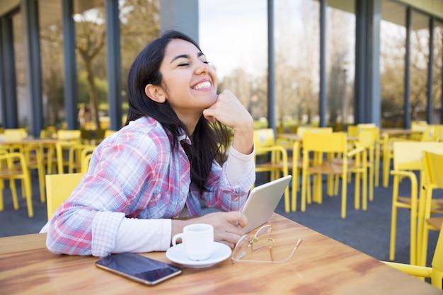 Lachende frau, die geräte verwendet und kaffee im café trinkt Kostenlose Fotos
