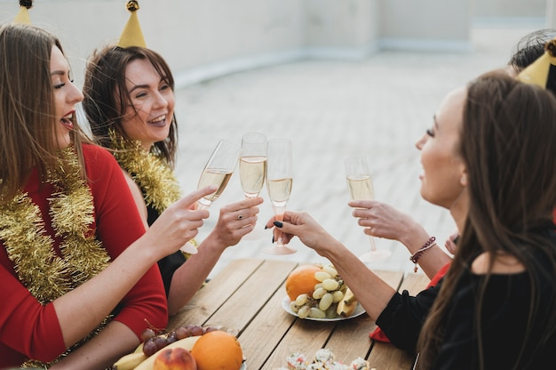 Lachende frauen, die gläser champagner aufmuntern