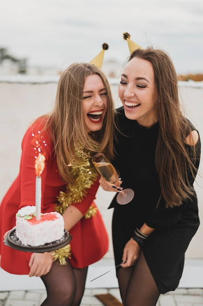 Lachende frauen in roten und schwarzen kleidern halten die geburtstagstorte und das sektglas Kostenlose Fotos