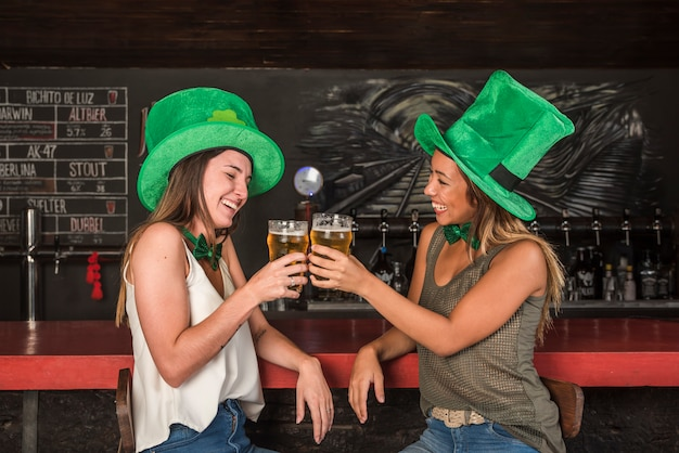 Lachende frauen in st.-patricks-hüten, die gläser am bar-theke trinken Kostenlose Fotos