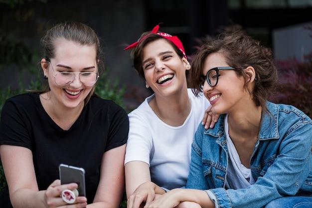 Lachende freunde, die smartphone im park betrachten Kostenlose Fotos
