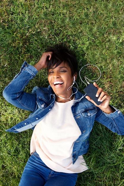 Lachende junge afrikanische frau, die auf gras mit kopfhörern und handy liegt Premium Fotos
