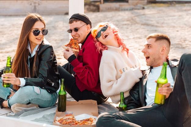 Lachende junge freunde, die spaß auf picknick haben Kostenlose Fotos