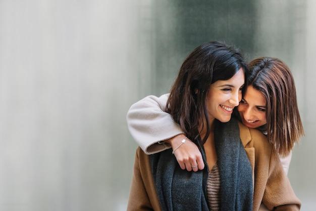 Lachende junge freundinnen, die in der liebe umarmen Kostenlose Fotos