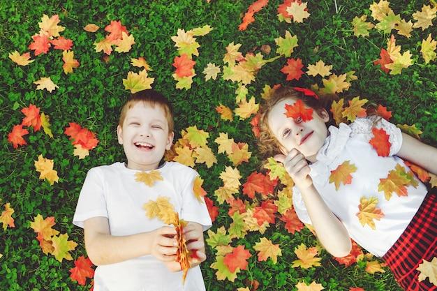 Lachende kinder, die im gras liegen, werfen den herbstlaub in der luft und zeigen sich daumen. Premium Fotos