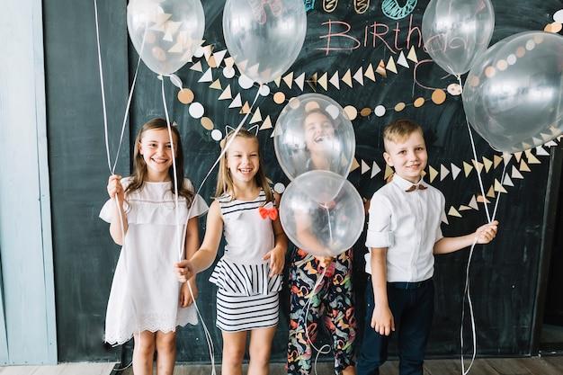 Lachende kinder mit weißen ballons Kostenlose Fotos