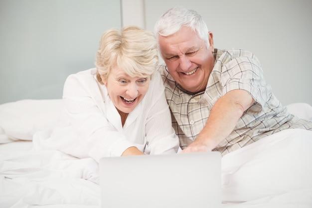 Lachende paare bei der anwendung des laptops im bett Premium Fotos