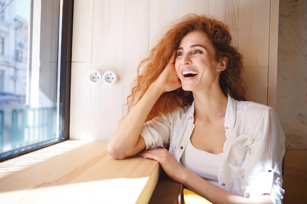 Lachende rothaarige junge dame, die im café sitzt. Kostenlose Fotos