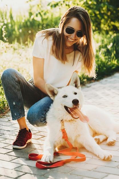 Lachende schöne junge frau in sommerkleidung und sonnenbrille, die auf hunkern mit ihrem weißen entzückten hund sitzt Premium Fotos