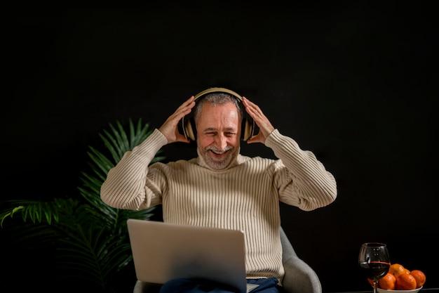 Lachender älterer mann, der auf kopfhörer sich setzt Kostenlose Fotos