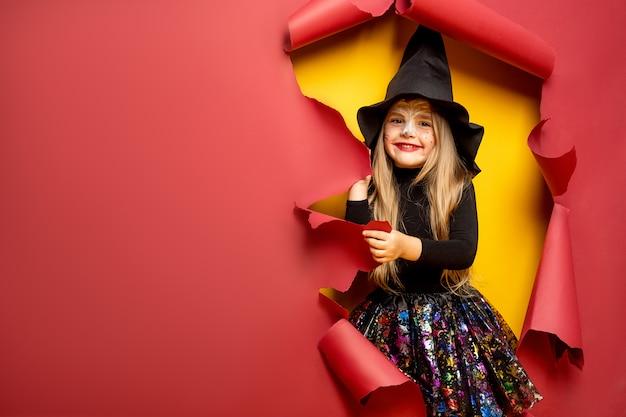 Lachendes lustiges kindermädchen in einem hexenkostüm in halloween Premium Fotos